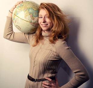 Jolee Evans Alum of Industrial Design, posing with a globe of the earth she is holding