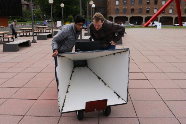 Two EECE students working on a project outside