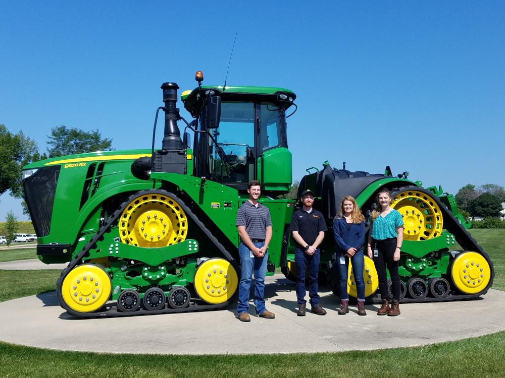 An image of a senior project group standing in front of a tractor for their project