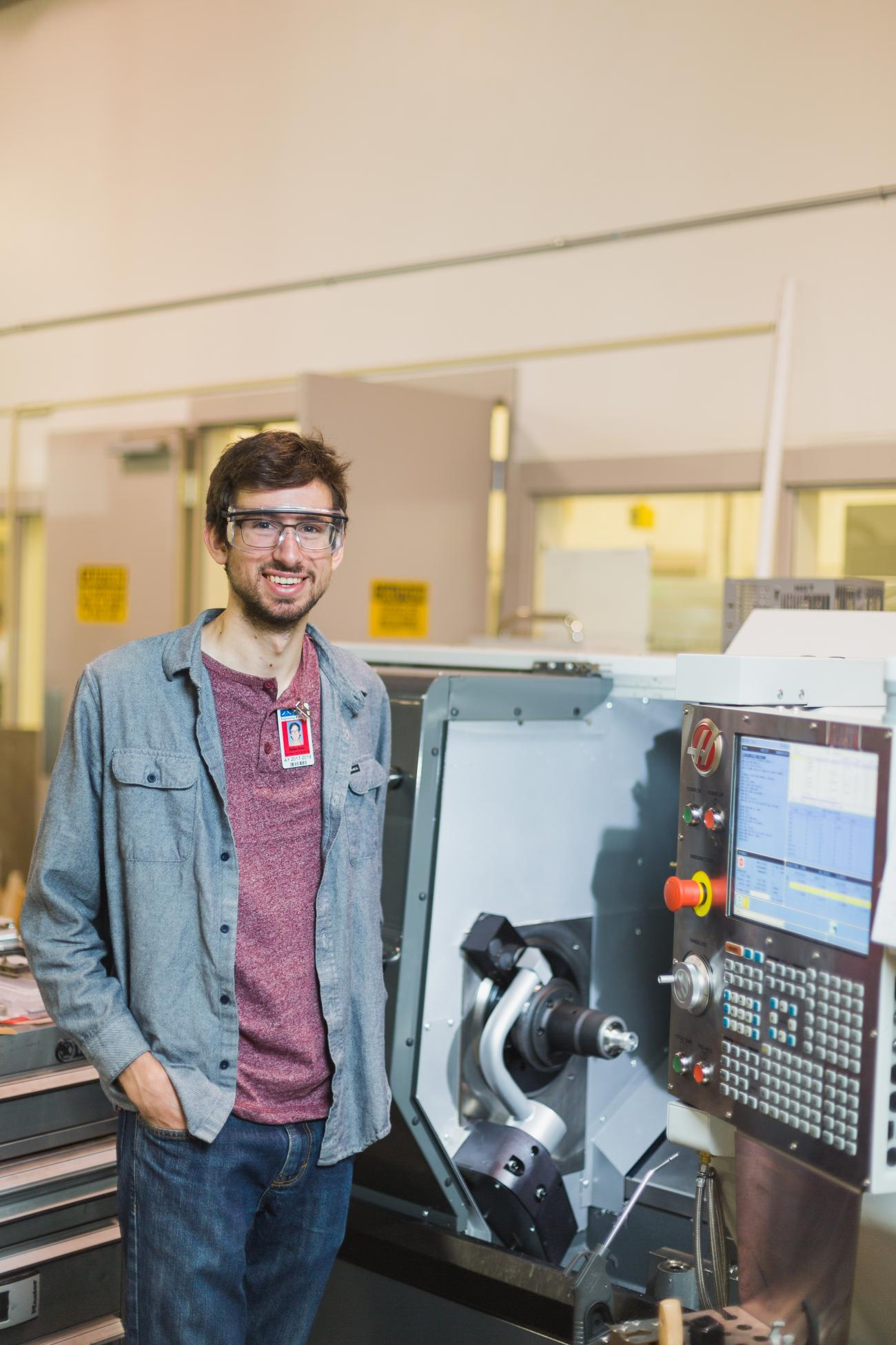 A Manufacturing Student standing next to a machine